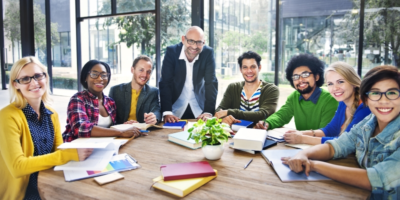 Group of people gathered around meeting table smiling at camera