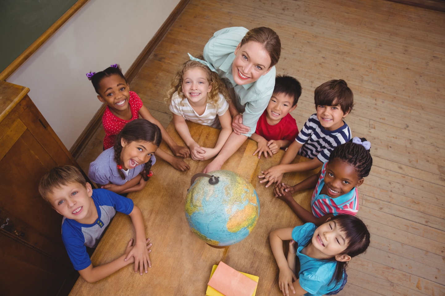 Children gathered around globe with a teacher