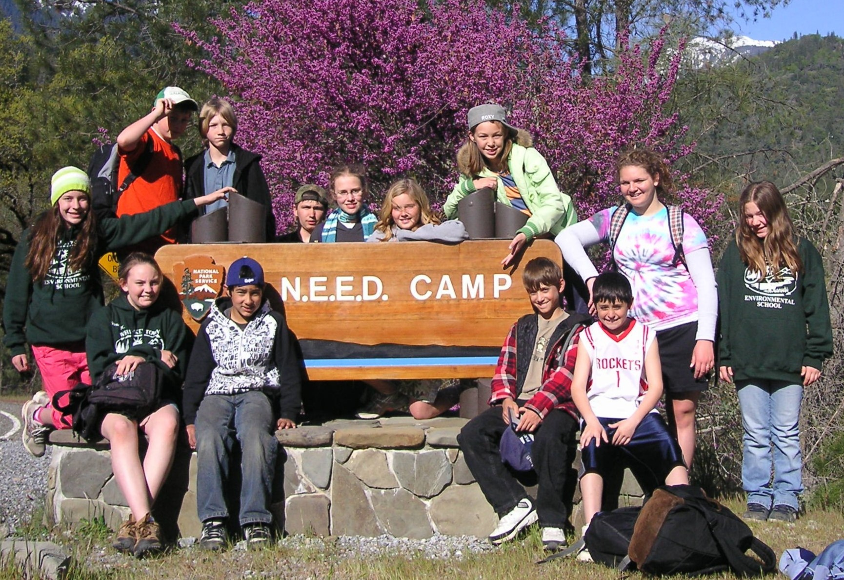 Kids standing around the NEED camp sign