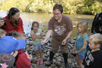 A field instructor standing near a creek holding baby frog in hand to show elementary school children that have gathered around her.