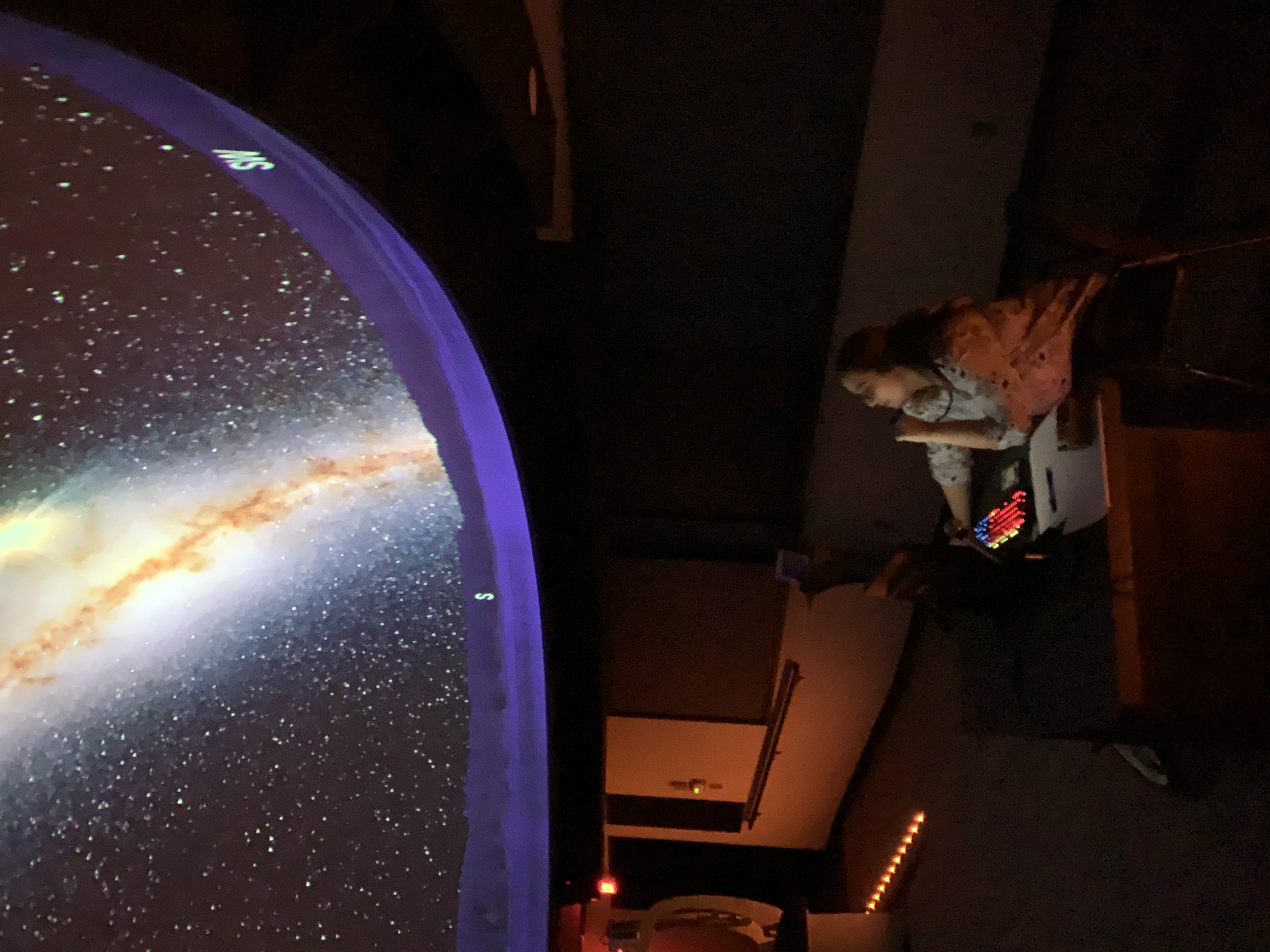 Photo of presenter and galaxy in the planetarium dome